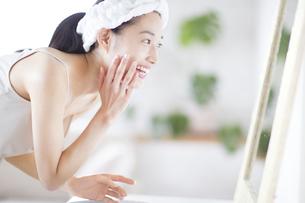 鏡の前でスキンケアをする笑顔の女性の写真素材 [FYI02966818]
