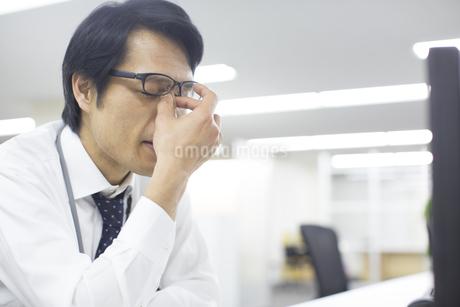 デスクで目を手でおさえるビジネス男性の写真素材 [FYI02966819]