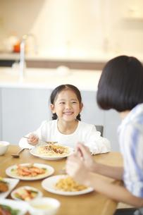 食事をしながら母に向いて笑う女の子の写真素材 [FYI02966820]