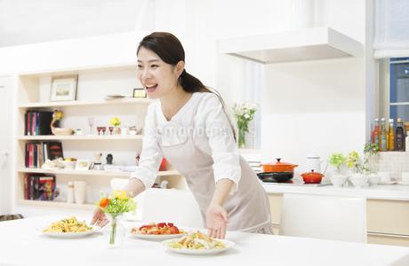食卓に料理を置いて声をかける奥さんの写真素材 [FYI02966824]
