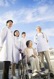 屋上で車椅子の患者に添う医師たちの写真素材 [FYI02966829]