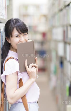 図書室で本を口元にあてて笑う女子学生の写真素材 [FYI02966830]