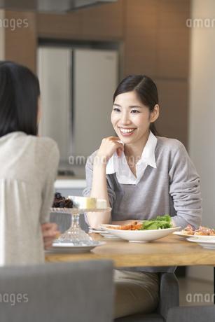 テーブルで食事を前に笑顔で会話する女性の写真素材 [FYI02966831]