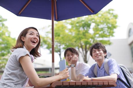 野外のテーブルに座って笑う3人の学生の写真素材 [FYI02966834]