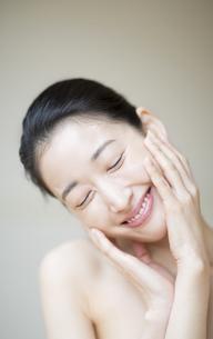 頬に両手を添えた笑顔の女性の写真素材 [FYI02966835]