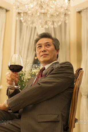 ワイングラスを手にポーズをとるシニア男性の写真素材 [FYI02966839]