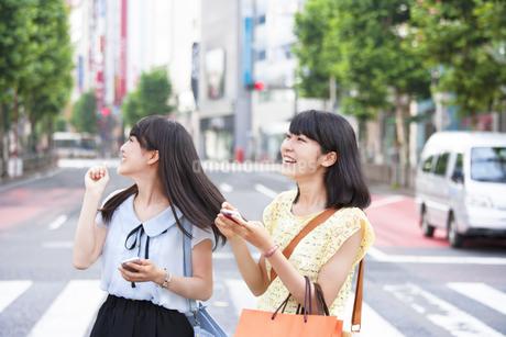 スマートフォンを持って歩く買物中の若い女性2人の写真素材 [FYI02966840]