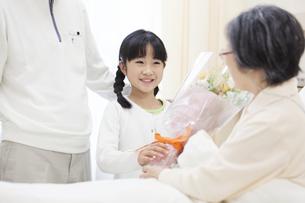 お見舞いにきて花束を渡す女の子の写真素材 [FYI02966844]