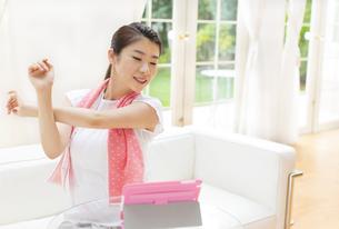 タブレットPCを見ながらストレッチをする女性の写真素材 [FYI02966846]