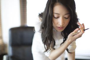 オフィスのデスクで前かがみで考え込むビジネス女性の写真素材 [FYI02966847]