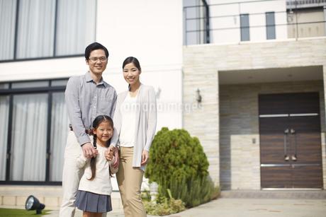 家の前に立つ3人家族の写真素材 [FYI02966853]