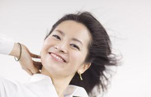 風を受けながら微笑む女性のアップの写真素材 [FYI02966857]