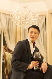 ワイングラスを手にポーズをとる若い男性の写真素材 [FYI02966866]