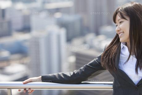 屋上で柵に腕をかけて微笑むビジネス女性の写真素材 [FYI02966868]