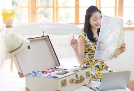 旅行の準備をする笑顔の女性の写真素材 [FYI02966871]