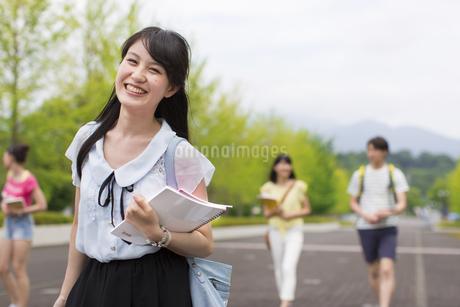 キャンパスを笑顔で歩く女子学生の写真素材 [FYI02966874]