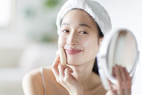 手鏡でスキンケアをする微笑む女性の写真素材 [FYI02966876]