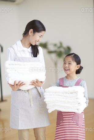 たたんだタオルを持って笑い合う親子の写真素材 [FYI02966878]