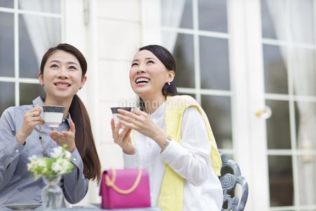 コーヒーカップを手に見上げる2人の女性の写真素材 [FYI02966880]
