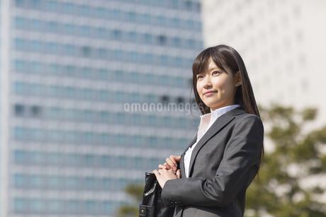ビルを背景に微笑むビジネス女性の写真素材 [FYI02966883]