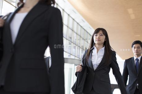 ビルのエントランスを歩くビジネス男女の写真素材 [FYI02966884]