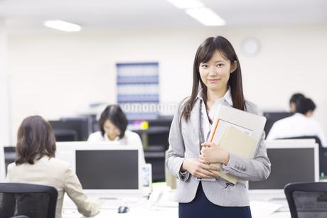 オフィスで立って微笑むビジネス女性の写真素材 [FYI02966885]