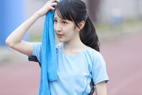陸上競技場でタオルで汗を拭いている女子学生の写真素材 [FYI02966886]