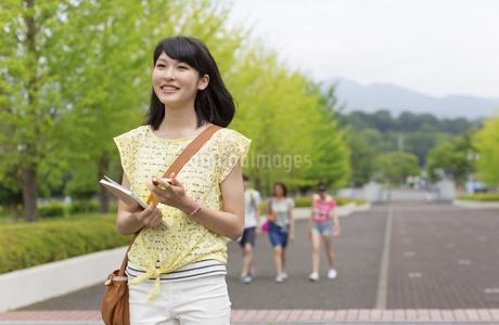 微笑みながらキャンパスを歩く女子学生の写真素材 [FYI02966890]
