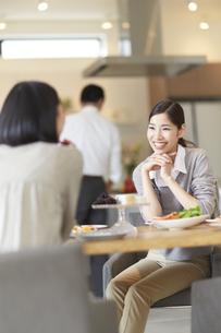 テーブルで食事を前に笑顔で会話する女性の写真素材 [FYI02966892]
