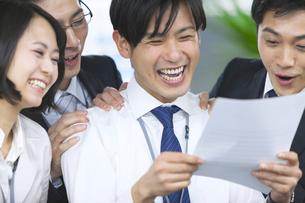 紙資料を見て喜ぶビジネス男女の写真素材 [FYI02966893]