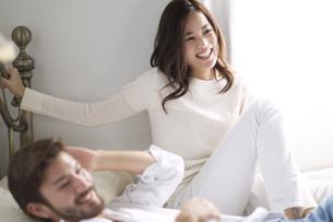 ベッドの上で微笑む男性と女性の写真素材 [FYI02966894]