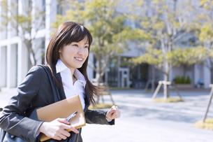 手帳を手に走るビジネス女性の写真素材 [FYI02966895]