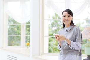 スマートフォンを持って微笑む女性の写真素材 [FYI02966897]