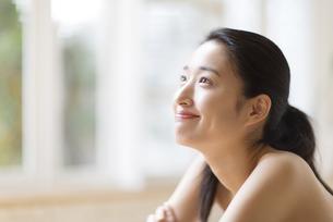 窓辺で上を見上げる笑顔の女性の写真素材 [FYI02966898]