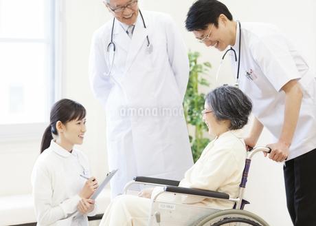 車椅子の患者に添う男性医師たちと女性看護師の写真素材 [FYI02966903]