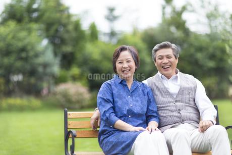 ベンチに掛けて笑うシニア夫婦の写真素材 [FYI02966904]