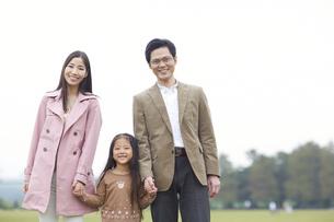 公園で手を繋いで微笑む家族のスナップの写真素材 [FYI02966907]