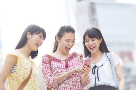 スマートフォンを見つめて喜ぶ3人の若い女性の写真素材 [FYI02966910]