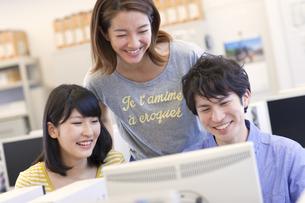 パソコン教室でモニターに向かう3人の学生の写真素材 [FYI02966911]