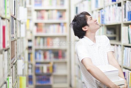 図書室で本を探す男子学生の写真素材 [FYI02966912]