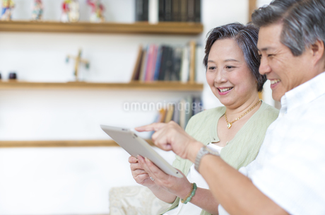 笑顔でタブレットPCを見るシニア夫婦の写真素材 [FYI02966914]