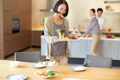 テーブルに食事を運ぶ女性の写真素材 [FYI02966918]