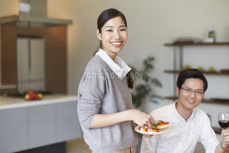 食事とワイングラスを手に笑う男女のスナップの写真素材 [FYI02966919]