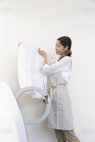 洗濯ものをみて微笑む主婦の写真素材 [FYI02966920]