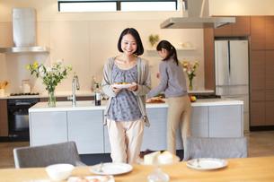 テーブルに食事を運ぶ女性の写真素材 [FYI02966921]