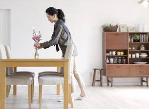 テーブルの上に花を立てる女性の横顔の写真素材 [FYI02966927]