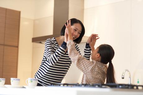 キッチンでハイタッチして笑い合う親子の写真素材 [FYI02966928]