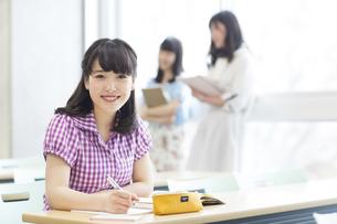 教室の席に座って微笑む女子学生の写真素材 [FYI02966930]