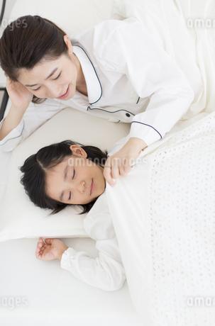眠る娘に布団をかける母親の写真素材 [FYI02966931]