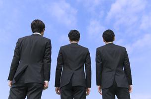 青空を背景に立つ3人のビジネス男性の後ろ姿の写真素材 [FYI02966932]
